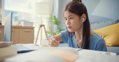 junge asiatische Mädchen Teenager mit Freizeitkleidung Kopfhörer verwenden Laptop-Computer online lernen Vorlesungsnotizbuch im Wohnzimmer im Haus schreiben. Isolieren Sie das Online-E-Learning-Konzept für die Coronavirus-Pandemie. foto
