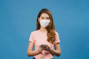 junges asiatisches mädchen, das medizinische gesichtsmaske mit handy trägt und in lässiger kleidung auf blauem hintergrund gekleidet ist. Selbstisolation, soziale Distanzierung, Quarantäne zur Vorbeugung des Coronavirus. foto