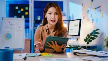 Asiatische Geschäftsfrau soziale Distanzierung in neuer Normalität für die Virenprävention, die sich die Kamerapräsentation an den Kollegen über den Plan im Videoanruf während der Arbeit in der Büronacht ansieht. Lebensstil nach dem Coronavirus. foto