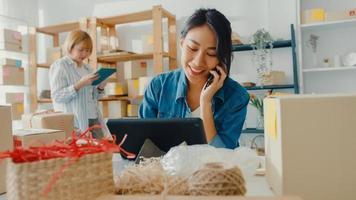 Junge Geschäftsfrauen in Asien, die einen Handyanruf verwenden, erhalten eine Bestellung und überprüfen das Produkt auf Lager im Home Office. Kleinunternehmer, Online-Marktlieferung, Lifestyle-Freelance-Konzept. foto