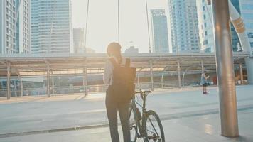 Asiatische Geschäftsfrau mit Rucksack trägt eine Antivirus-Schutzmaske vor Coronavirus und macht einen Fahrradspaziergang auf einer Stadtstraße, um im Büro zu arbeiten. zur Arbeit pendeln, Berufspendler für das Covid-19-Konzept. foto