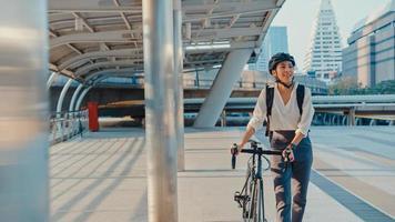 asiatische geschäftsfrau gehen im büro spazieren und lächeln tragen rucksack schauen sich um, nehmen fahrrad auf der straße um das gebäude auf einer stadtstraße. Fahrradpendeln, Pendeln mit dem Fahrrad, Geschäftspendlerkonzept. foto