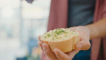 Hand der jungen asiatischen Köchin verteilt Knoblauchbutter auf rustikalem Roggenbrot mit Metallmesser auf Holzbrett auf Küchentisch im Haus. frische hausgemachte Brotproduktion, gesunde Ernährung und traditionelle Bäckerei. foto