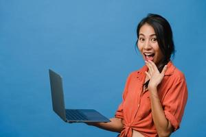 Überraschte junge Asiatin mit Laptop mit positivem Ausdruck, breites Lächeln, in Freizeitkleidung gekleidet und mit Blick auf die Kamera auf blauem Hintergrund. glückliche entzückende frohe frau freut sich über erfolg. foto