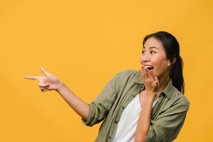 Porträt einer jungen asiatischen Dame, die mit fröhlichem Ausdruck lächelt, zeigt etwas Erstaunliches an leeren Stellen in Freizeitkleidung und steht einzeln auf gelbem Hintergrund. Gesichtsausdruck Konzept. foto