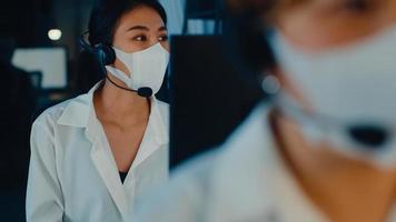 Millennial Asia Young Call Center Team oder Customer Support Service Executive, die Gesichtsmaske tragen, verhindern, dass Covid-19 mit Computer- und Mikrofon-Headsets technische Unterstützung im Late-Night-Büro leistet. foto