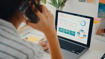 Junge Asia Business Lady Anruf Handy mit Kollegen im Unternehmen über Arbeitsfinanzierung Diagramm Marktplan in Laptop und Tablet im Haus. Mädchen lernen online, arbeiten von zu Hause aus. foto
