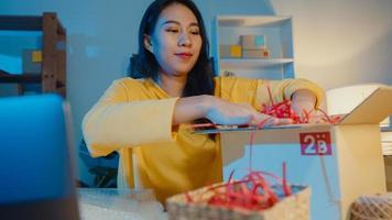 junge asiatische frau verpackung box paket verwenden papier für unterstützungsprodukt leichte schäden zerbrechliches produkt im heimbüro in der nacht. Kleinunternehmer, Online-Marktlieferung, Lifestyle-Freelance-Konzept. foto