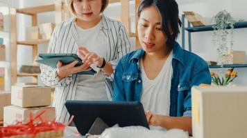 Junge Geschäftsfrauen in Asien, die sich treffen, Produktbestellung auf Lager überprüfen und auf Tablet-Computerarbeit im Home Office speichern. Kleinunternehmer, Online-Marktlieferung, Lifestyle-Freelance-Konzept. foto
