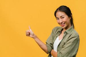 Porträt einer jungen asiatischen Dame, die mit fröhlichem Ausdruck lächelt, zeigt etwas Erstaunliches an leeren Stellen in legerem Tuch und blickt auf die Kamera einzeln auf gelbem Hintergrund. Gesichtsausdruck Konzept. foto