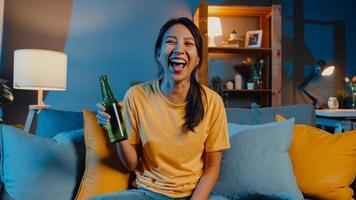 Fröhliche junge asiatische frau, die in die kamera schaut, genießen die nächtliche partyveranstaltung online mit freunden trinkt bier per videoanruf online im wohnzimmer zu hause, bleibt zu hause quarantäne, konzept der sozialen distanzierung. foto