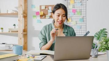 Asiatische Geschäftsfrau, die Laptop verwendet, spricht mit Kollegen über den Plan im Videoanruf, während sie intelligent von zu Hause aus im Wohnzimmer arbeitet. Selbstisolation, soziale Distanzierung, Quarantäne zur Vorbeugung des Coronavirus. foto