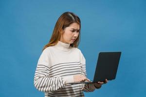 junge asiatische dame mit laptop mit negativem ausdruck, aufgeregtem schreien, emotional wütend in lässigem tuch weinen und auf blauem hintergrund mit leerem kopierraum isoliert stehen. Gesichtsausdruck Konzept. foto