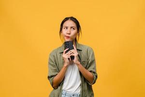 Denken träumende junge asiatische Dame mit Telefon mit positivem Ausdruck, gekleidet in lässiges Tuch, das Glück fühlt und isoliert auf gelbem Hintergrund steht. glückliche entzückende frohe frau freut sich über erfolg. foto