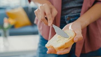 Hände einer jungen asiatischen Köchin, die Butter auf rustikalem Roggenbrot mit einem Metallmesser auf einem Holzbrett auf dem Küchentisch im Haus verteilt. frische hausgemachte Brotproduktion, gesunde Ernährung und traditionelle Bäckerei. foto
