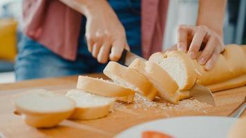 Hände einer jungen asiatischen Köchin, die ein Messer hält, das Vollkornbrot auf einem Holzbrett auf dem Küchentisch im Haus schneidet. frische hausgemachte Brotproduktion, gesunde Ernährung und traditionelles Bäckereikonzept. foto
