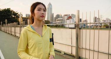 Schöne junge asiatische Sportlerin trainiert mit dem Smartphone, um Musik beim Laufen in der städtischen Umgebung zu hören. koreanisches jugendlich Mädchen, das am frühen Morgen Sportkleidung auf der Gehwegbrücke trägt. foto