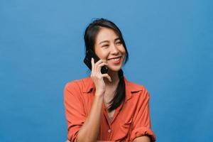 junge asiatische Dame telefoniert mit positivem Ausdruck, lächelt breit, in Freizeitkleidung gekleidet, fühlt sich glücklich und steht isoliert auf blauem Hintergrund. glückliche entzückende frohe frau freut sich über erfolg. foto