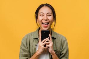 überraschte junge asiatische dame, die handy mit positivem ausdruck benutzt, breit lächelt, in lässiger kleidung gekleidet ist und die kamera auf gelbem hintergrund betrachtet. glückliche entzückende frohe frau freut sich über erfolg. foto