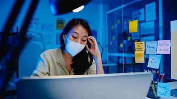 freiberufliche asiatische frauen tragen gesichtsmaske mit harter arbeit des laptops im neuen normalen büro. Arbeit von zu Hause aus Überlastung in der Nacht, Selbstisolation, soziale Distanzierung, Quarantäne zur Vorbeugung von Coronaviren. foto