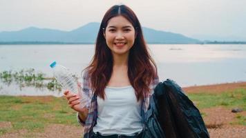 porträt junger asiatin-freiwilliger helfen, die natur sauber zu halten, indem sie plastikflaschenabfälle und schwarze müllsäcke am strand halten. Konzept über Umweltverschmutzung Probleme. foto