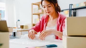 junge asiatische unternehmerin geschäftsfrau, die produkt in karton verpackt, an den kunden liefert und im heimbüro arbeitet. Kleinunternehmer, Online-Marktzustellung starten, Lifestyle-Freelance-Konzept. foto