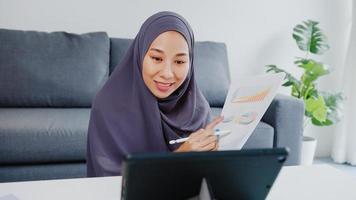 asiatische muslimische dame tragen kopftuch beiläufiger gebrauch tablet sprechen mit kollegen über verkaufsbericht in konferenz-videoanrufen, während sie von zu hause im wohnzimmer arbeiten. soziale Distanzierung, Quarantäne wegen Corona-Virus. foto
