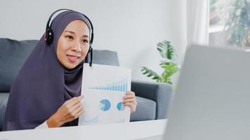 asiatische muslimische dame tragen kopfhörer mit laptop sprechen mit kollegen über verkaufsbericht in konferenz-videoanrufen, während sie von zu hause im wohnzimmer arbeiten. soziale Distanzierung, Quarantäne wegen Corona-Virus. foto