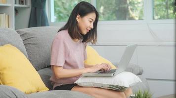 junge, freiberufliche asiatische frau, die am laptop arbeitet und soziale medien überprüft, während sie auf dem sofa liegt, wenn sie sich zu hause im wohnzimmer entspannt. Lebensstil lateinische und hispanische ethnische Frauen im Hauskonzept. foto