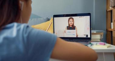 junges asiatisches Mädchen mit gelegentlichem Gebrauch von Computer-Laptop-Videoanrufen online lernen mit dem Lehrer, der Vorlesungsnotizbuch im Wohnzimmer im Haus schreibt. Isolieren Sie das Online-E-Learning-Konzept für die Coronavirus-Pandemie. foto