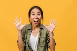 junge asiatische dame fühlen sich glücklich mit positivem ausdruck, freudiger überraschung funky, gekleidet in lässigem tuch und betrachten die kamera einzeln auf gelbem hintergrund. glückliche entzückende frohe frau freut sich über erfolg. foto