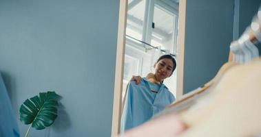 schöne attraktive asiatische dame, die kleidung auf kleiderständer auswählt, die sich im spiegel im wohnzimmer des hauses anzieht. Mädchen denken, was lässiges Hemd zu tragen. Lifestyle-Frauen entspannen sich zu Hause Konzept. foto