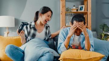 glückliches asiatisches junges paar mann und frau sitzen auf der couch und verwenden einen Joystick-Controller, um ein Videospiel zu spielen, verbringen lustige Zeit zusammen im Wohnzimmer. asiatisches Ehepaar Familienleben, Paar bleibt zu Hause Konzept. foto