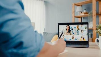 junge asiatische geschäftsleute, die laptop verwenden, sprechen mit kollegen über plan in videoanrufbesprechungen, während sie von zu hause im wohnzimmer arbeiten. Selbstisolation, soziale Distanzierung, Quarantäne zur Vorbeugung des Coronavirus. foto