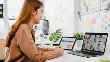 Asiatische Geschäftsleute, die Laptop verwenden, sprechen mit Kollegen, die ein Geschäfts-Brainstorming über den Plan in einem Videoanruf-Meeting in einem neuen normalen Büro diskutieren. Lebensstil soziale Distanzierung und Arbeit nach dem Coronavirus. foto