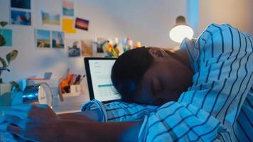 freiberufliche asien erschöpfte dame harte arbeit, die im neuen normalen heimbüro schläft. Arbeiten von Hausüberlastung in der Nacht, aus der Ferne, Selbstisolation, soziale Distanzierung, Quarantäne zur Vorbeugung von Coronaviren. foto
