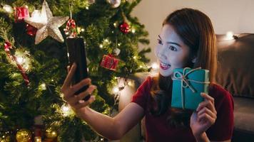 junge asiatische Frau mit Smartphone-Videoanruf im Gespräch mit Paar mit Weihnachtsgeschenkbox, Weihnachtsbaum mit Ornament im Wohnzimmer zu Hause verziert. Weihnachtsnacht und Neujahrsfest. foto