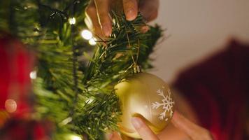 asiatische Frau mit Ornament am Weihnachtsbaum in der Weihnachtsnacht und Neujahrsfest zu Hause dekoriert. Weihnachtsfeier Event Vorbereitung oder Winterferien Festival Indoor Party. Nahaufnahme. foto