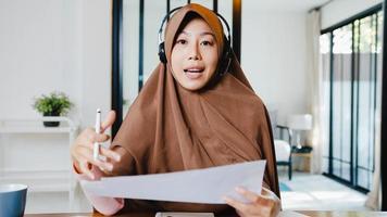 asiatische muslimische dame tragen kopfhörer mit computer-laptop sprechen mit kollegen über verkaufsbericht in videoanrufen, während sie von zu hause im wohnzimmer aus der ferne arbeiten. soziale Distanzierung, Quarantäne wegen Corona-Virus. foto