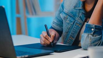 Fröhliche junge Grafikdesignerin mit digitalem Grafiktablett, während sie nachts im modernen Büro spät arbeitet, asiatische Berufsfrau mit Laptop-Retusche, die zu Hause im Wohnzimmer sitzt. foto