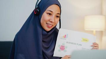 asiatische muslimische dame tragen kopfhörer mit laptop sprechen sie mit kollegen über verkaufsbericht in konferenz-videoanrufen, während sie nachts im heimbüro arbeiten. soziale Distanzierung, Quarantäne wegen Corona-Virus. foto