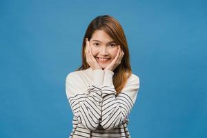 junge asiatische dame mit positivem ausdruck, breit lächeln, in lässigem tuch gekleidet und auf blauem hintergrund isoliert in die kamera schauen. glückliche entzückende frohe frau freut sich über erfolg. Gesichtsausdruck Konzept. foto