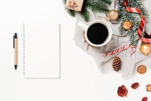 minimale kreative flache Lage der traditionellen Winterweihnachtskomposition und der Neujahrsferienzeit. Ansicht von oben offenes Mockup schwarzes Notebook für Text auf weißem Hintergrund. Mock-up und kopieren Sie Raumfotografie. foto