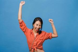 junge asiatische dame mit positivem ausdruck, fröhlich und aufregend, gekleidet in lässiges tuch über blauem hintergrund mit leerem raum. glückliche entzückende frohe frau freut sich über erfolg. Gesichtsausdruck Konzept. foto