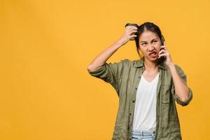junge asiatische dame spricht per telefon mit negativem ausdruck, aufgeregtem schreien, weinen emotional wütend in lässigem tuch und steht einzeln auf gelbem hintergrund mit leerem kopierraum. Gesichtsausdruck Konzept. foto