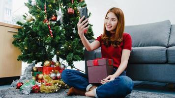 Junge asiatische Frau mit Smartphone-Videoanruf im Gespräch mit Paar mit Weihnachtsgeschenkbox, Weihnachtsbaum mit Ornament im Wohnzimmer zu Hause geschmückt. Weihnachts- und Neujahrsfest. foto