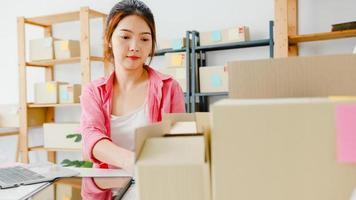 Junge asiatische Unternehmerin Geschäftsfrau Produktbestellung auf Lager überprüfen und auf Computer-Laptop-Arbeit im Home-Office speichern. Kleinunternehmer, Online-Marktlieferung, Lifestyle-Freelance-Konzept. foto
