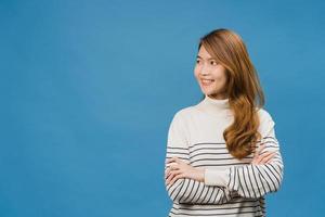 Porträt einer jungen asiatischen Dame mit positivem Ausdruck, verschränkten Armen, breitem Lächeln, in Freizeitkleidung gekleidet und mit Blick auf den Weltraum auf blauem Hintergrund. glückliche entzückende frohe frau freut sich über erfolg. foto