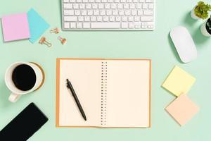 kreatives flaches Laienfoto des Arbeitsplatzschreibtisches. Schreibtisch von oben mit Tastatur, Maus und offenem schwarzen Notizbuch auf pastellgrünem Hintergrund. Draufsichtmodell mit Kopienraumfotografie. foto