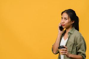 junge asiatische dame spricht per telefon und hält kaffeetasse mit negativem ausdruck, aufgeregtem schreien, weinen emotional wütend in lässigem tuch und steht einzeln auf gelbem hintergrund. Gesichtsausdruck Konzept. foto